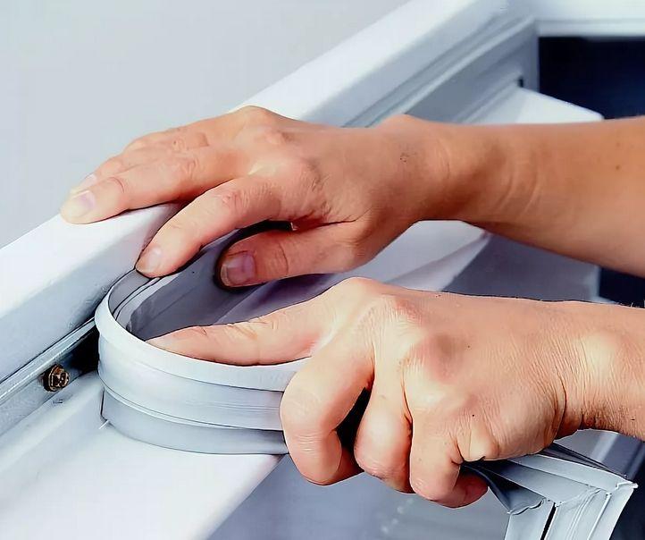 Мастер устанавливает уплотнительную резину холодильника